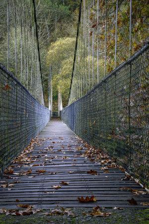 Steel and wooden suspension bridge with autumnal leaves in Seivane Lugo Galicia