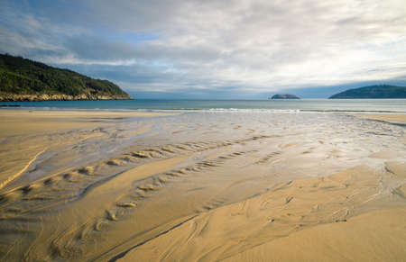 A stream of fresh water flows into a beach creating patterns in the sand in Bars in Galicia Banco de Imagens