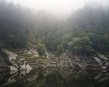 Slate cliffs covered in misty forest rush into the waters of the river near Portomarin Galicia Banco de Imagens