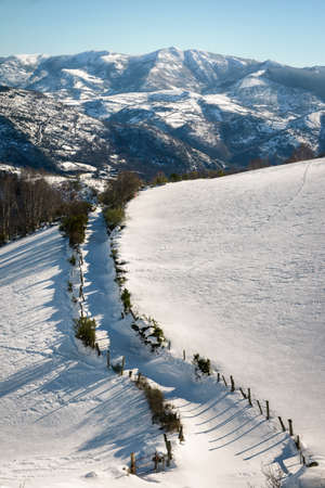 Snowy landscape with a path between fields and mountains in the background in Seoane do Courel Galicia