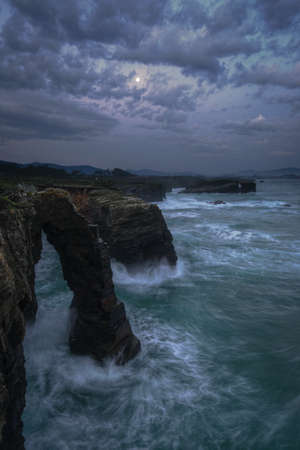 Iconic rock arches illuminated by the full moon at As Catedrais beach in Galicia Banco de Imagens