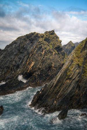Black slate cliffs crossed by veins of golden pyrite in Loiba Ortigueira Coast geopark Galicia