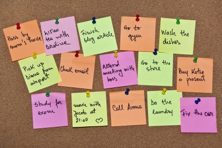 wooden post: A collection of multi coloured post it notes with different messages on a wooden background Stock Photo