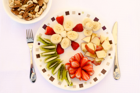 Fruits on a plate with nuts in bowl Banque d'images