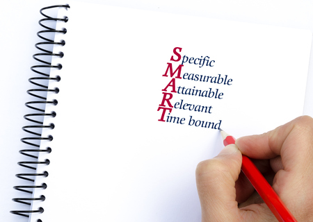 specific: Acronym SMART as Specific, Measurable, Attainable, Relevant, Time bound written on notebook. Conceptual image