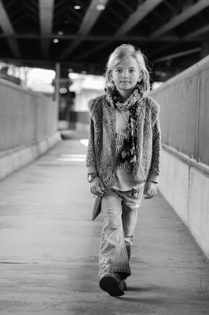 Young pretty little girl walking along the street. Monochrome full length portrait