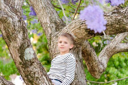Blonde boy, enjoying nature, outdoor in spring. Jacaranda trees