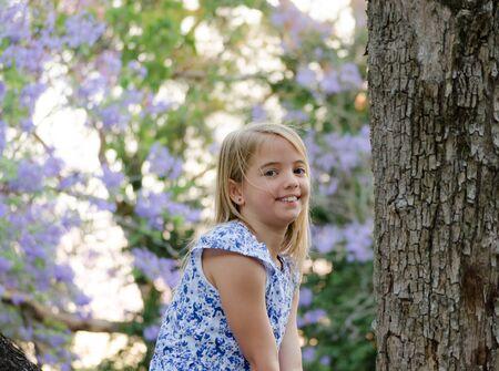 Blonde girl, enjoying nature, outdoor in spring. Jacaranda trees