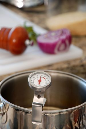 thermometer and kitchen with stainless steel pot of onion to the bottom Stock Photo