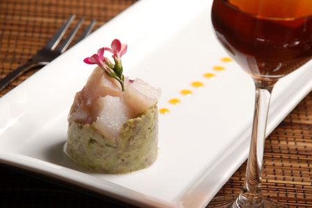 raw fish on plate decorated with glass of wine photo