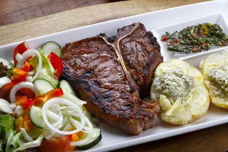 t bone steak: t bone steak with potato salad and vegetables