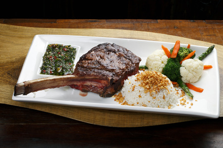 t bone: t bone steak with potato salad and vegetables