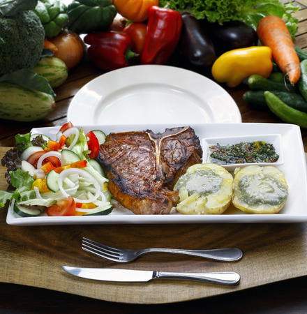t bone: t bone steak with potato salad and vegetables