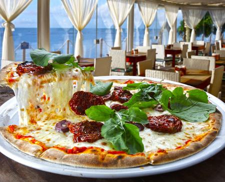Pizza with dried tomatoes, rucula and mozzarella in pizzeria overlooking the sea Foto de archivo