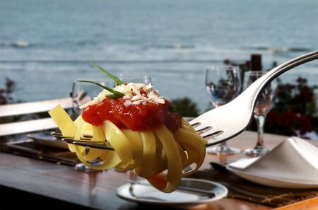 Pasta with tomato sauce on fork with table for dinner by the sea