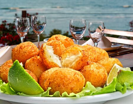 salt cod fritters on the beach Imagens