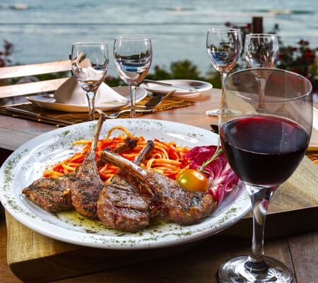 Lamb rib with pasta and glass of red wine with the sea in the background