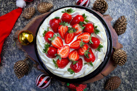 Cake with white chocolate icing, whipped cream and strawberries and Christmas decoration