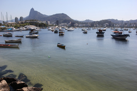 despite: Rio de Janeiro, Brazil, 12 September, 2016: Christ the Redeemer statue is seen from Urca, place used as small fishing boats dock. Despite being bathed by the waters of Guanabara Bay, the water was crystal clear and at some points you could see fish swimmi