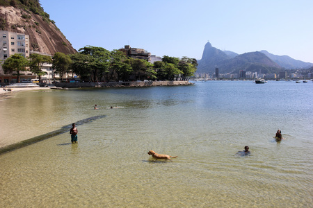 Rio de Janeiro, Brazil, 12 September, 2016: Children play with dog on the Urca Beach. Spring is approaching and the weather in Rio de Janeiro starts to get warmer. On a sunny and hot afternoon people get excited to leave home to enjoy the natural beauty o Editorial
