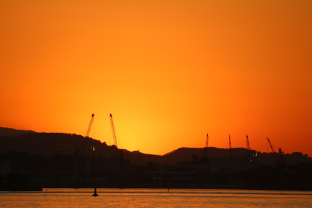 despite: Rio de Janeiro, Brazil, July 14, 2017: View of the sunset in winter afternoon in the port area of Rio de Janeiro. Cariocas and tourists watch the sun set on the shores of Guanabara Bay, in the center of Rio. Despite winter, temperatures in the city are in