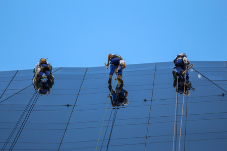 View of mountaineers cleaning the glass facade of a large building in downtown Rio. The commercial mountaineering profession is risky, but its workers have a beautiful view from above. Image produced on July 29, 2017, in downtown Rio de Janeiro, Brazil.