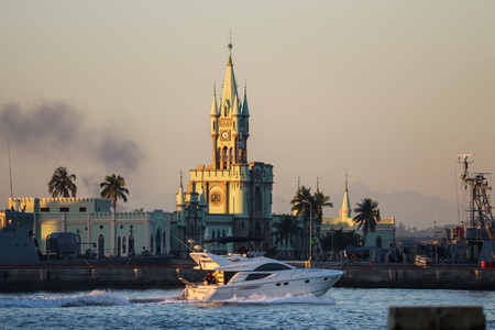 Rio de Janeiro, Brazil, August 7, 2017: Rio de Janeiro has sunny and hot afternoon in winter. In this image, speedboat sails in front of historic building of the Fiscal Island during sunset seen from the Guanabara Bay, Downtown Rio.
