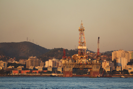 Rio de Janeiro, Brazil, August 7, 2017: Rio de Janeiro has sunny and hot afternoon in winter.oil platform anchored in Niteroi during sunset seen from Guanabara Bay, Downtown Rio.