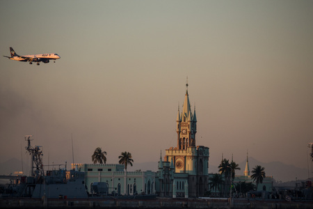 Rio de Janeiro, Brazil, August 7, 2017: Rio de Janeiro has sunny and hot afternoon in winter.Azuls airplane overhead fleets historic building from Fiscal Island during sunset seen from Guanabara Bay, Downtown Rio.