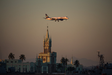 Rio de Janeiro, Brazil, August 7, 2017: Rio de Janeiro has sunny and hot afternoon in winter. Azuls airplane overhead fleets historic building from Fiscal Island during sunset seen from Guanabara Bay, Downtown Rio.