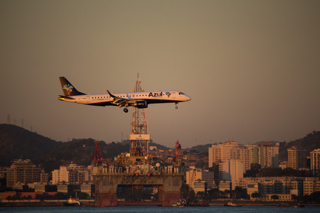 Rio de Janeiro, Brazil, August 7, 2017:  Azuls airplane overflys the waters of Guanabara Bay and passes in front of the petroleum platform anchored in the vicinity of Santos Dumont Airport, Downtown Rio.