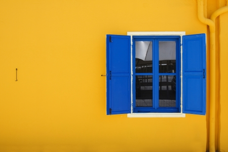 window  glass: Yellow mediterranean house with blue window