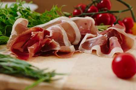 parma ham: Parma ham and fresh raw tomatos and herbs, basil and rosemary served to eat on a wooden cutting board. Concept of serving a rustic snack