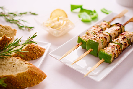 restaurant setting: Barbeque Grilled chicken and peppers on skewer served on rectangular plate in restaurant setting with Macedoine dipping sauce and bread. Stock Photo