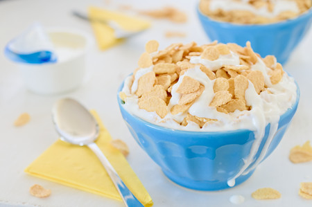 greek pot: Cornflake cereals with greek yogurt in blue ceramic pot and two drips on the side with open yogurt and yellow napkins in background.