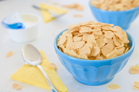 greek pot: Cornflake cereals with greek yogurt in blue ceramic pot with open yogurt and yellow napkins in background.