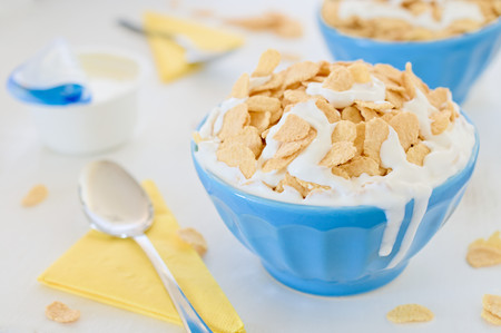 greek pot: Cereali cornflake con yogurt greco in blu vaso di ceramica e due gocce sul lato aperto con yogurt e tovaglioli gialli in background.