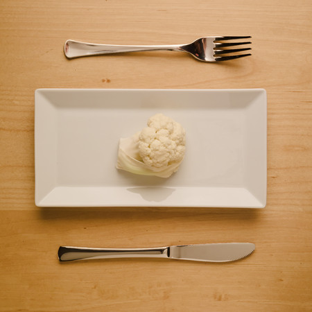 top down: Concept of vegan and vegetarian low-carb diet. A single raw cauliflower on a square rectangle plate with table knife and fork. Top down view.