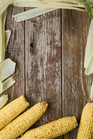 top down: Top down corn with corn husk surrounding rustic wooden table