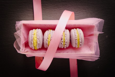 top down: Homemade lavender macaroons with vanilla cream in pink box with pink ribbon. Top down view. Flat lay.