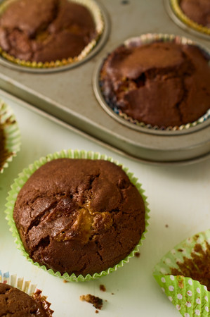 comfort food: Concept of comfort food. Freshly baked homemade chocolate chip muffins on white table