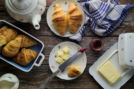 top down: Concept of afternoon snack. Concept of afternoon tea. Home-baked puff pastry butter croissants with marmalade and tea in rustic setting. Top down view. Stock Photo