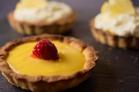 home baking: Delicious sweet dessert fresh cheese with lemon and vanilla with raspberry tarts on dark stone slate. Selective focus on lemon slice. Concept of Home baking. Concept of home made desserts.