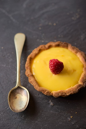 home baking: Delicious sweet dessert vanilla cream tart decorated with raspberry on dark stone slate. Selective focus on lemon slice. Concept of Home baking. Concept of home made desserts. Stock Photo