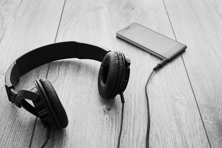 earpiece: Black smartphone and black headphones on wood background. Selective focus on right earpiece of headphones. Black and white.