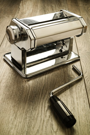 hand crank: Metal reflective pasta machine with separated hand crank wood surface. Selective focus on pasta machine.