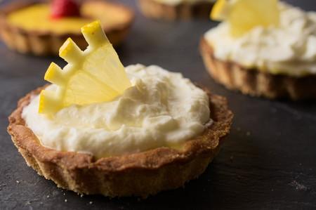 home baking: Delicious dessert fresh cheese and lemon tart decorated with lemon slice on dark stone slate. Selective focus on lemon slice. Concept of Home baking. Concept of home made desserts. Stock Photo