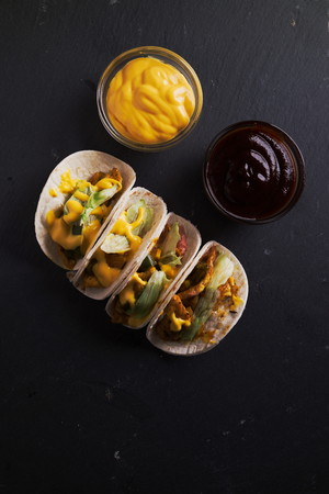 nacho: Homemade fresh chicken fajita tortilla tacos with peppers, lettuce and corn. bbq sauce, nacho cheese. Flat lay. Top down view. Negative space.