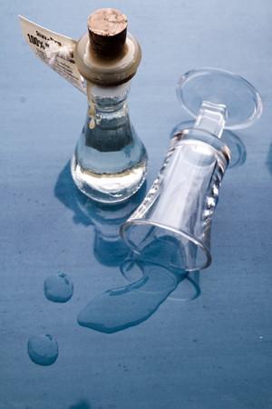ciruela pasa: 100% de cosecha propia elegido a dedo aguardiente de ciruela orgánicos con vaso derramado en el fondo del gradiente de reflexión con licor derramado. Foto de archivo