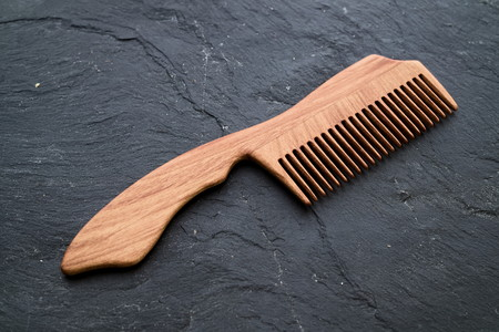 top down: Handmade handcrafted wood haircomb on dark stone slab background. Flat lay, top down view. Stock Photo